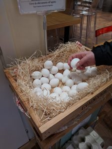 A basket of eggs for sale, with a hand holding one egg.